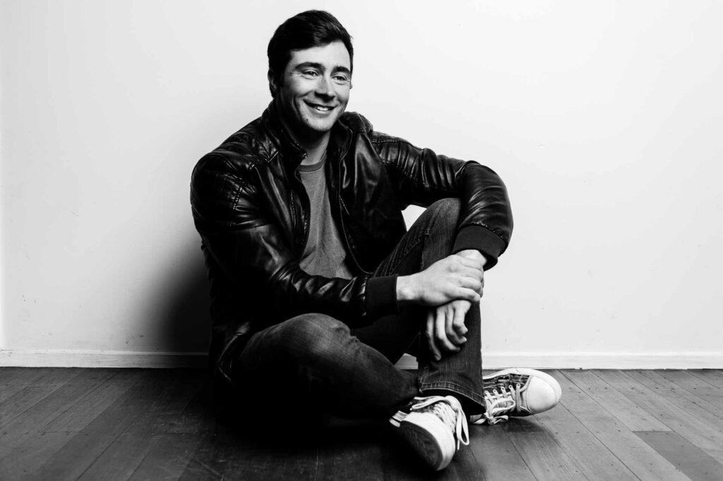 Jake Baker, legs crossed black & white portrait on timber floor